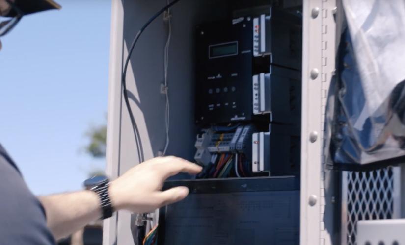 Le Groupe LML | Gros plan d'une main devant un panneau électrique