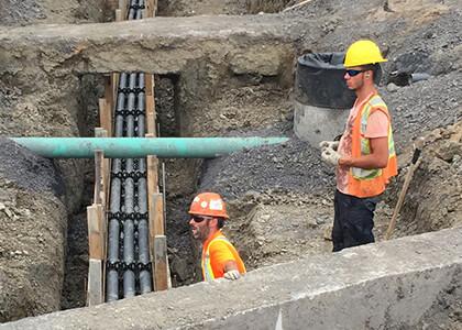 Le Groupe LML | Travailleurs en vestes oranges dans un trou