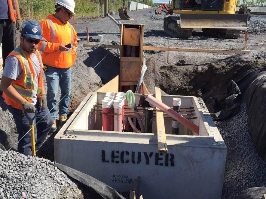 Le Groupe LML   Pelle électrique jaune et travailleurs de la construction