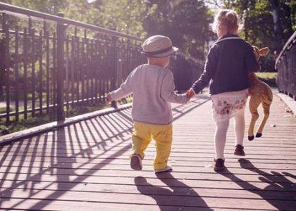 Le Groupe LML | Enfants de dos se tenant par la main à l'extérieur